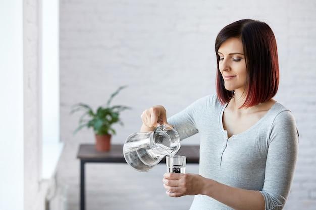 水を飲んでいる。健康的な生活様式。ダイエットのコンセプト。健康的な食事。美しい若い女性は、水を飲む。