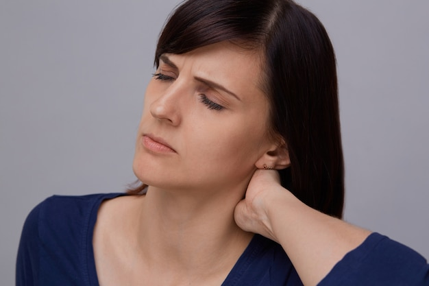 Крупным планом портрет молодой женщины, страдающей от зубной боли, держа пальцы челюсти и закрывая глаза от боли.