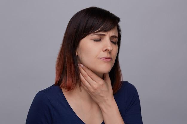 歯痛に苦しんで、顎に指を押し、痛みから目を閉じて若い女性のクローズアップの肖像画。