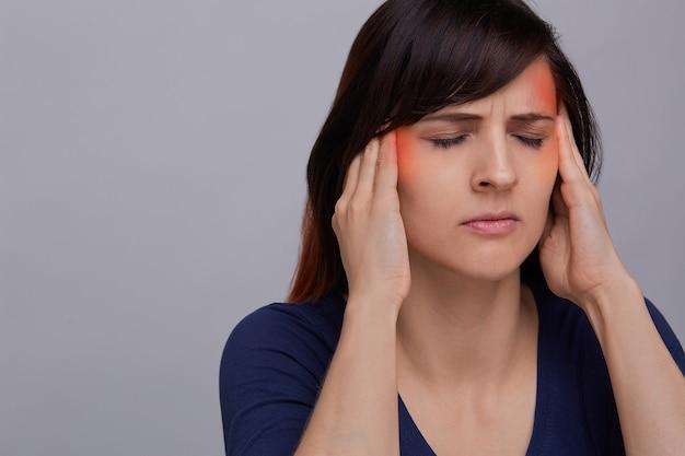 強い頭痛に苦しんでいる灰色の背景に若い女性のクローズアップの肖像画