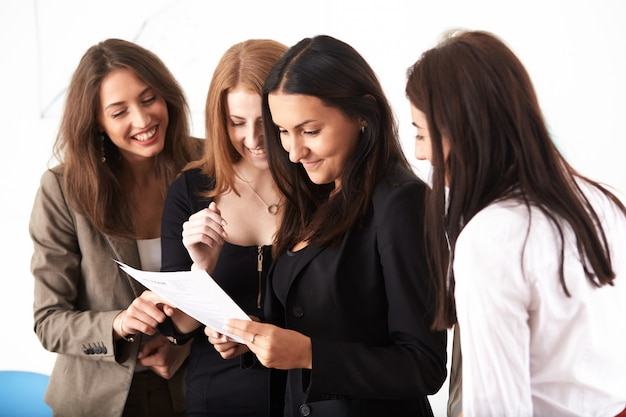Молодые усмехаясь бизнес-леди работая новый проект на офисе.