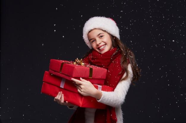 暗い背景に赤いサンタ帽子で美しい笑顔少女の肖像画