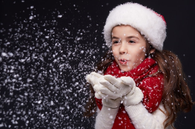 Портрет молодой красивой улыбающейся девушки в красной шапке санты на темном фоне