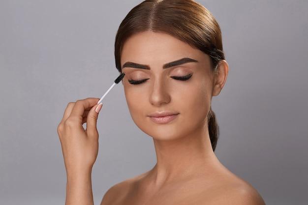マスカラ。化粧品、新鮮な柔らかい肌、化粧ブラシでマスカラを塗る長い黒の濃いまつげ。まつげエクステンション。偽まつげ。