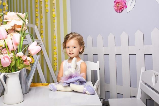 おもちゃを演奏する美しい少女。青い目のブロンド。