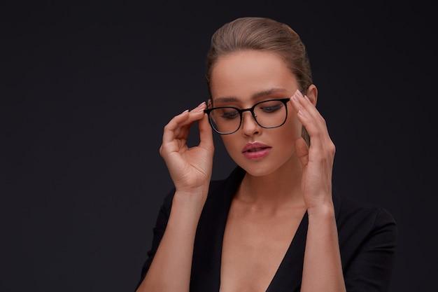 正方形の眼鏡でエレガントな深刻な女性。スーツで大人の美しい女性実業家
