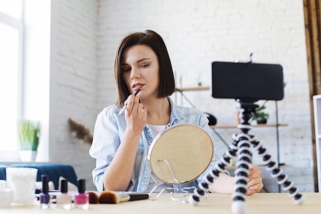 化粧品に関する彼女の美容ブログのチュートリアルビデオを記録する若い女性ブロガー