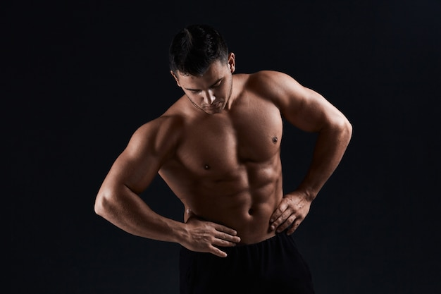 Мускулистый культурист на черном. сильный спортивный человек показывает тело, мышцы живота, грудные мышцы, бицепс и трицепс. утомляйтесь, набирая вес. бодибилдинг.