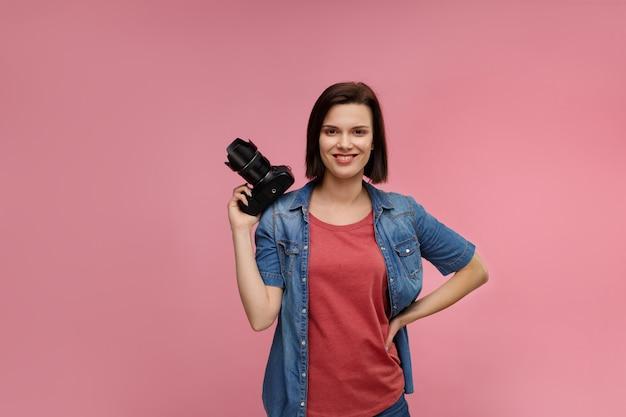 Портрет молодого женского фотографа изолированного на розовой предпосылке с космосом экземпляра.