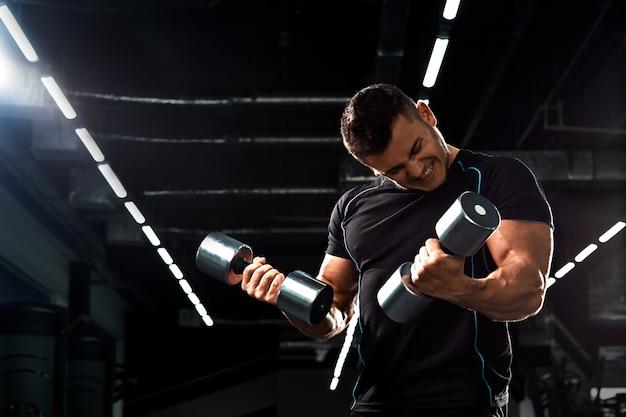 Мускулистые культурист, делать упражнения с гантелями в тренажерном зале. сильный спортивный человек показывает тело, мышцы живота, бицепс и трицепс. потренируйтесь, набирая вес, накачивая мышцы с гантелями.