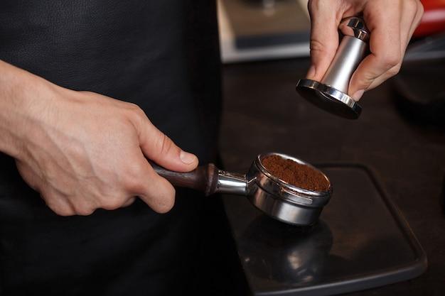 Молодой самец бариста вдавливает молотый кофе в бездонный держатель переносного фильтра с помощью тампера