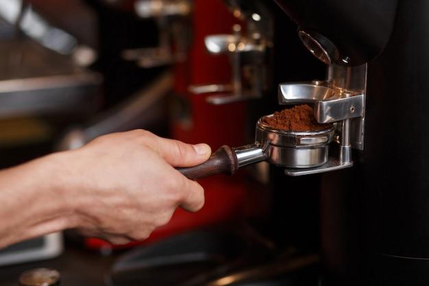 Бариста держит бездонный держатель портафильтра с молотым кофе