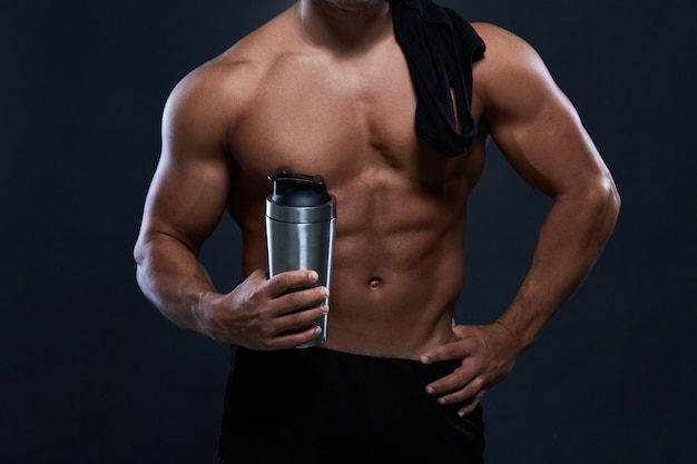 Мускулистый культурист с бутылкой шейкер на черном. сильный спортивный человек показывает тело, мышцы живота, грудные мышцы, бицепс и трицепс. бодибилдинг.