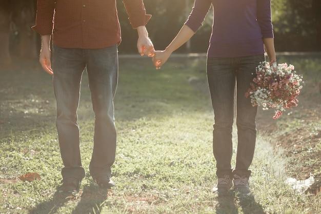 永遠の愛として一緒に手をつないでいる幸せな夫婦。