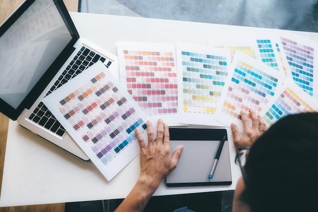 Графический дизайнер и цветные образцы и ручки на столе.