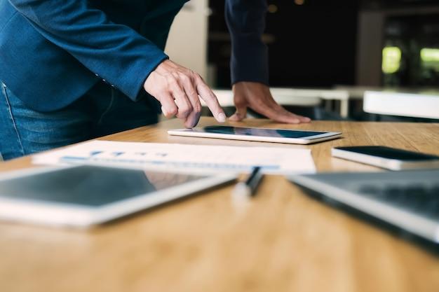 タブレットを使用しているビジネスマンはデータを分析します。