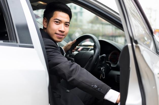 若い実業家は彼の車のドアを開きます