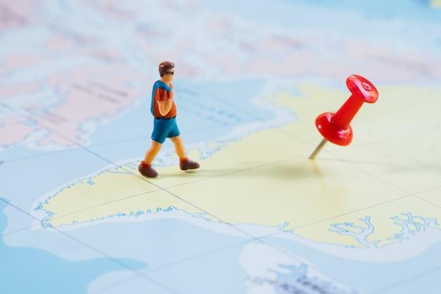 赤い押しピンと地図旅行コンセプトのミニフィギュア旅行者