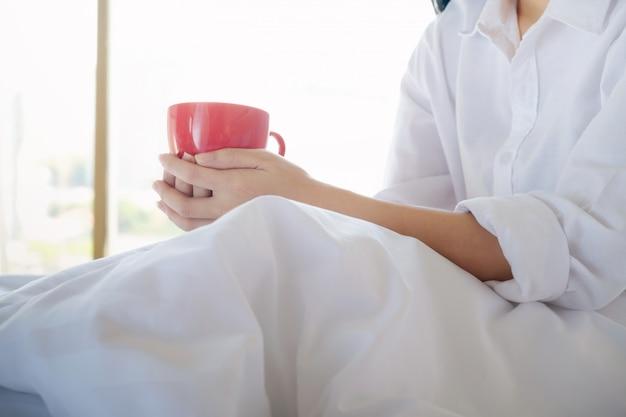ベッドに座っている彼女のコーヒーを楽しむリラックスした女性。