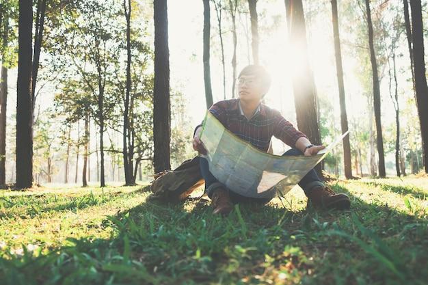 若い人旅行者は屋外でリラックスできるバックパックを持っています。
