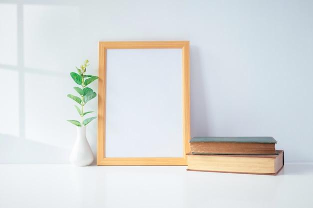 テーブル、家の装飾の緑の植物と肖像画の写真のフレームをモックアップ。