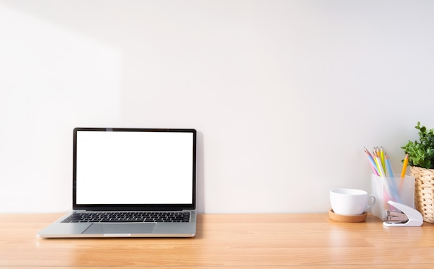 作業スペースと白いスクリーンラップトップ。