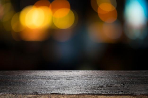 空の木製テーブルプラットフォームと夜のボケ