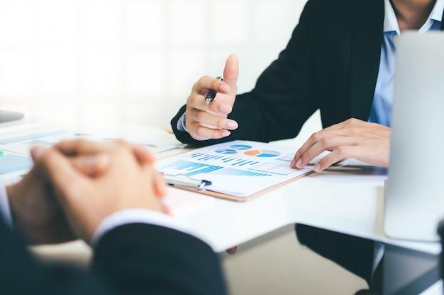 ビジネスマンチームワークミーティングで投資を議論する。