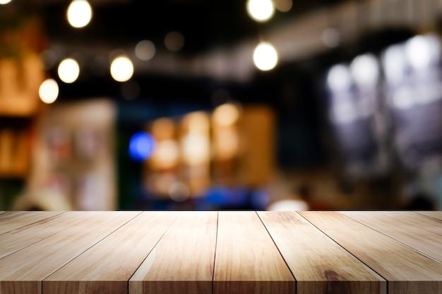 コーヒーショップの背景をぼかした写真を木製のテーブル。