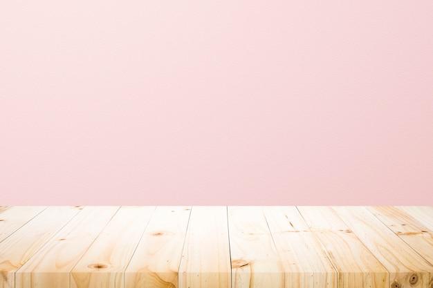 現在の製品のさびたピンクの背景の上の空の木製デッキテーブル。
