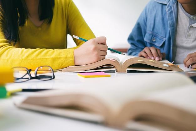 若い学生のキャンパスは友人が追いついて学ぶのを助けます。