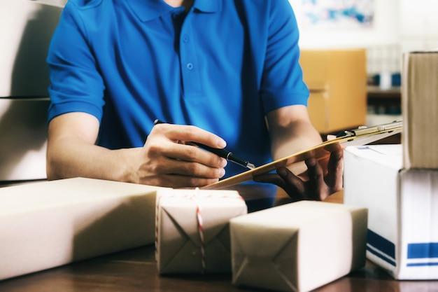 Курьер проверяет список получения доставки в офисе.