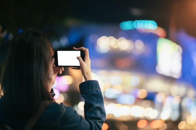 Путешественник молодой женщины принимая фото с мобильным телефоном.