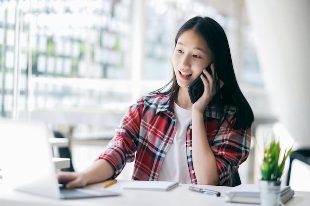 若いオフィスの女性がクライアントと携帯電話で話しています。