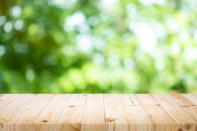 緑のボケ味を持つ現在の製品のための空のテーブル