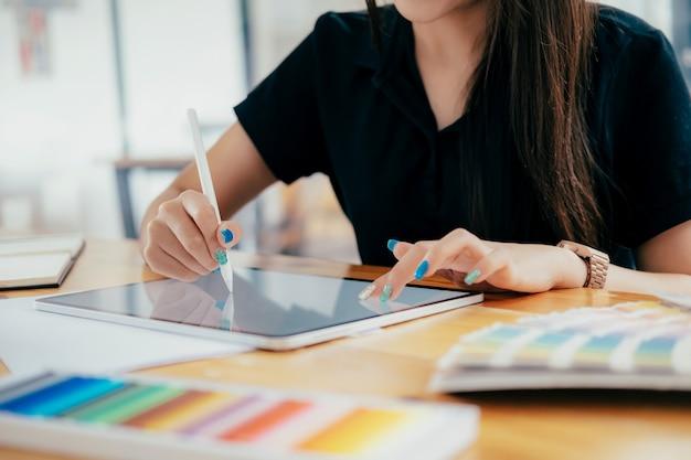 Графический дизайнер, работающий на ее столе в офисе творческой студии.
