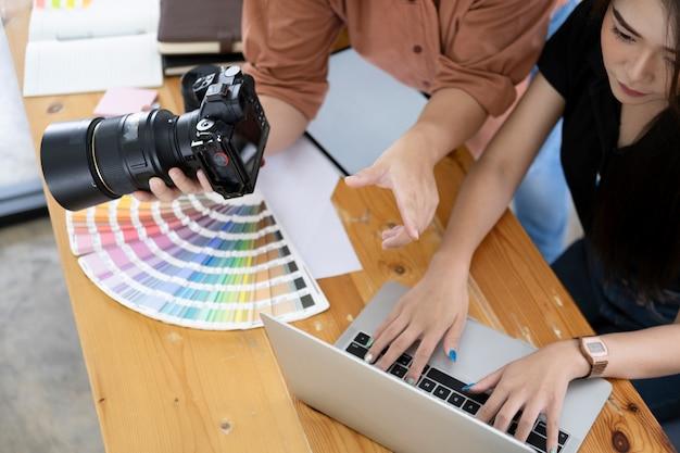 カメラから写真を選択する写真家とグラフィックデザイナー。