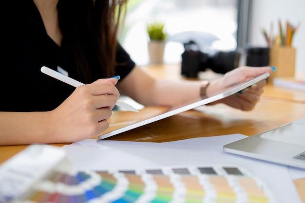 クリエイティブスタジオオフィスのデスクで働くグラフィックデザイナー。