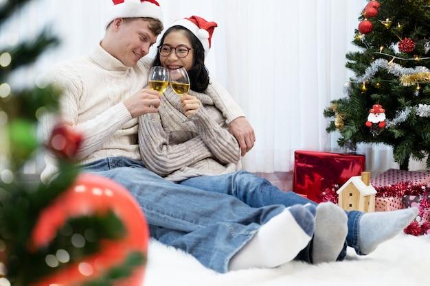 若いカップルがクリスマスのお祝いにシャンパングラスで乾杯します。