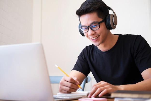 若い男が自宅で勉強してラップトップを使用して、オンライン学習