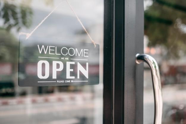 オープンとドアの看板を格納する歓迎のクローズアップ。