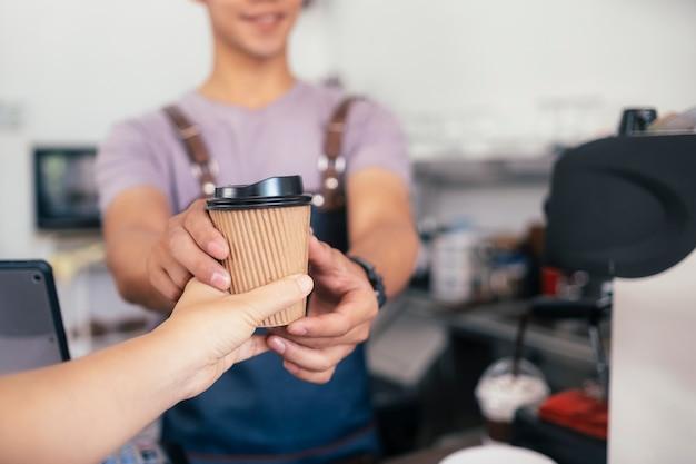 Молодой владелец кафе-кафе обслуживает клиентов.