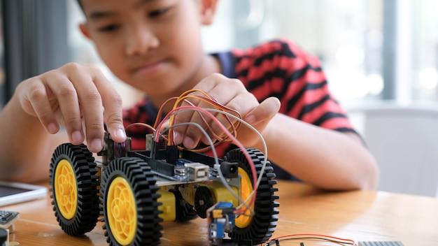 Сконцентрированный мальчик создавая робота на лаборатории.