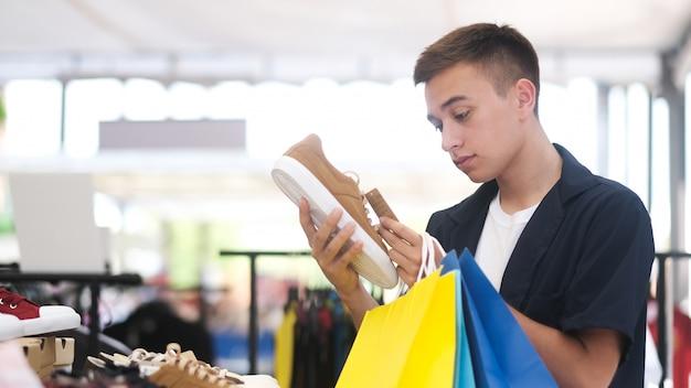 若い男は、ショッピングモールで買い物をしながら靴を選んでいます。