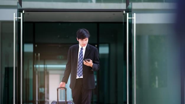 荷物を持って旅行するビジネスマン。