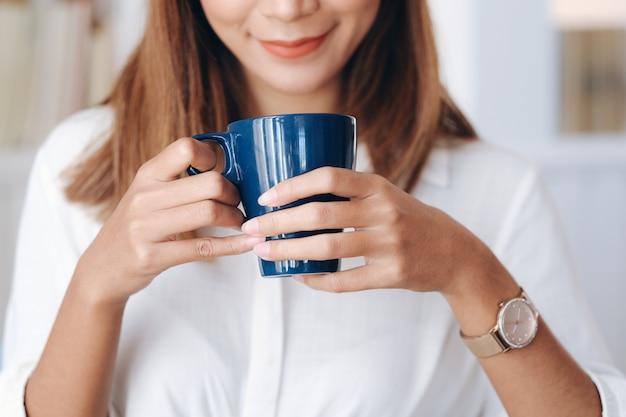 一杯のコーヒーを保持している女性。