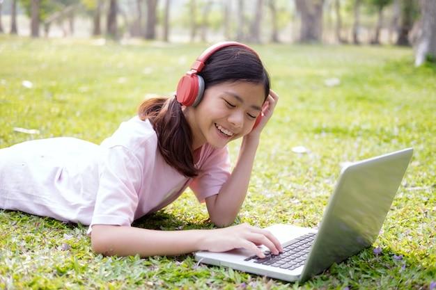 リラックスして音楽コンセプトを聴く。ワイヤレスヘッドフォンを持つ少女は、公園の音楽を聴く。