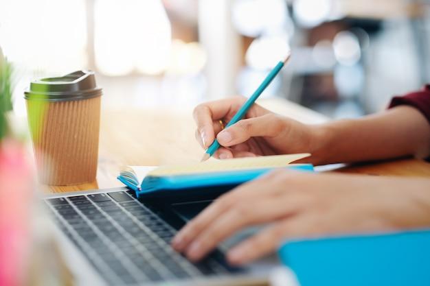 ノートに書くペンで女性の手を閉じます。