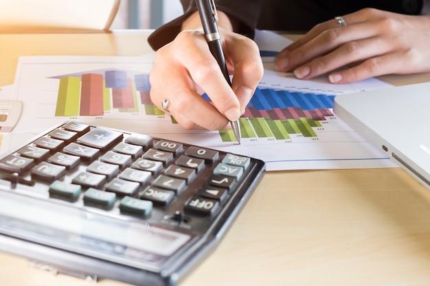 実業家の手が目標のチャートを指している。