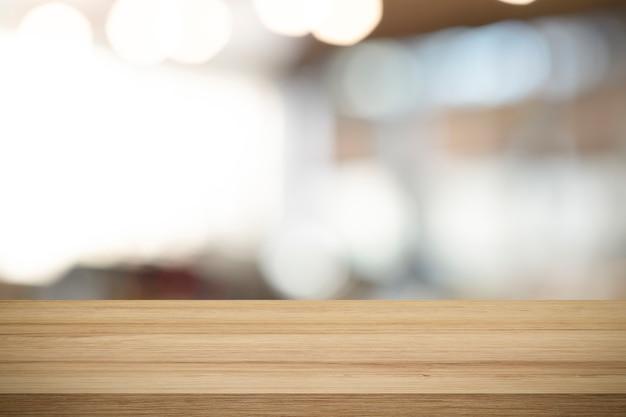コーヒーショップで現在の製品の空の木製テーブルは、背景をぼかし。
